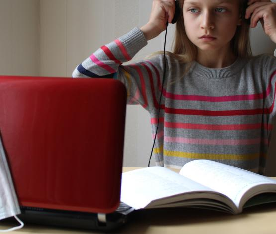 image of child at laptop with facemask