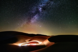 A clear night sky of stars over sand dunes